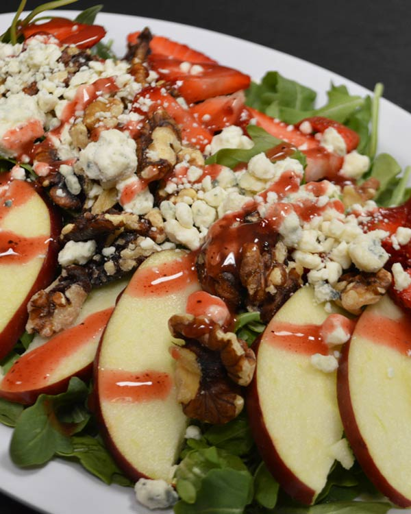 Italian Food - Signature Salad With Goat Cheese, Walnuts, and Apples Over A bead Of Fresh Spinach