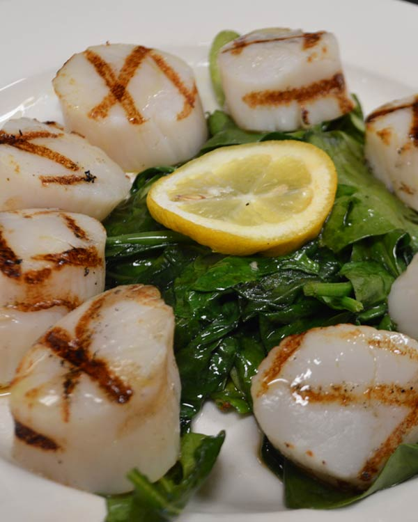 Grilled Scallops With Fresh Lemon Over A Bead Of Spinach
